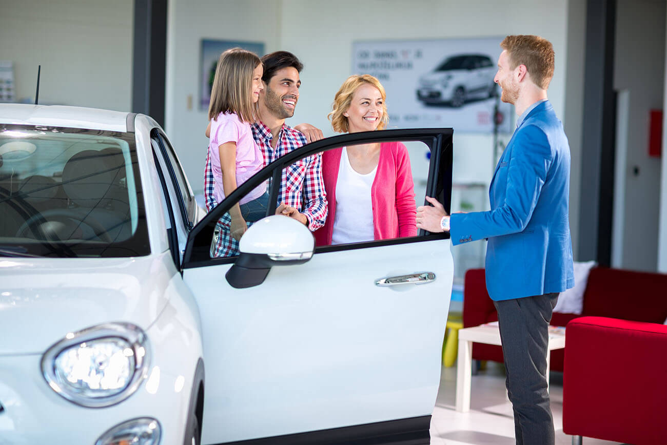 Family who have previously been declined car finance are in a showroom next to an open car they could be approved for