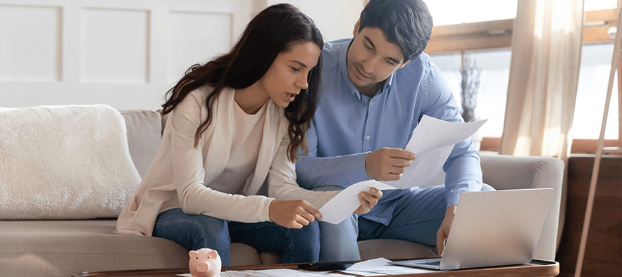 Couple sitting on sofa with paperwork and laptop looking concerned after being declined car finance