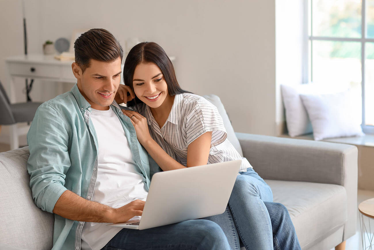 Happy couple on sofa with laptop looking for car finance in Essex