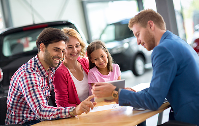 A happy couple with their child, speaking with a salesperson about benefits car finance