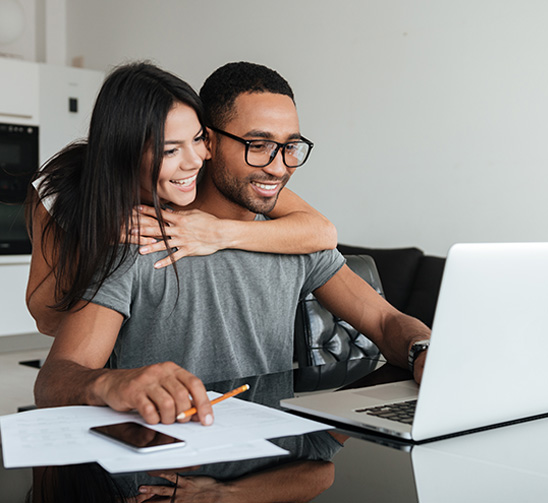 Happy couple looking at laptop applying for poor credit car finance