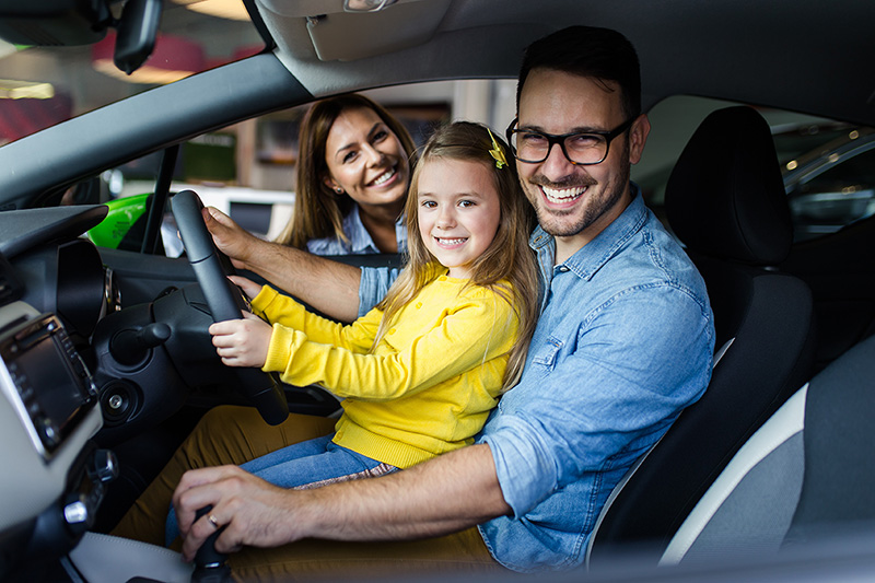 Family of three sitting in car happy with getting specialist car finance