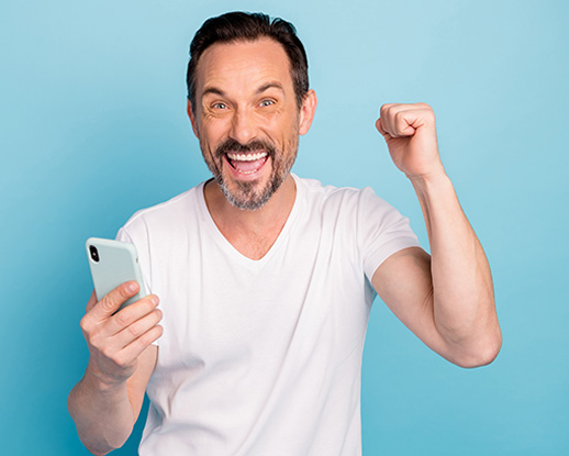 Man in white t-shirt happy with approval for car finance with defaults