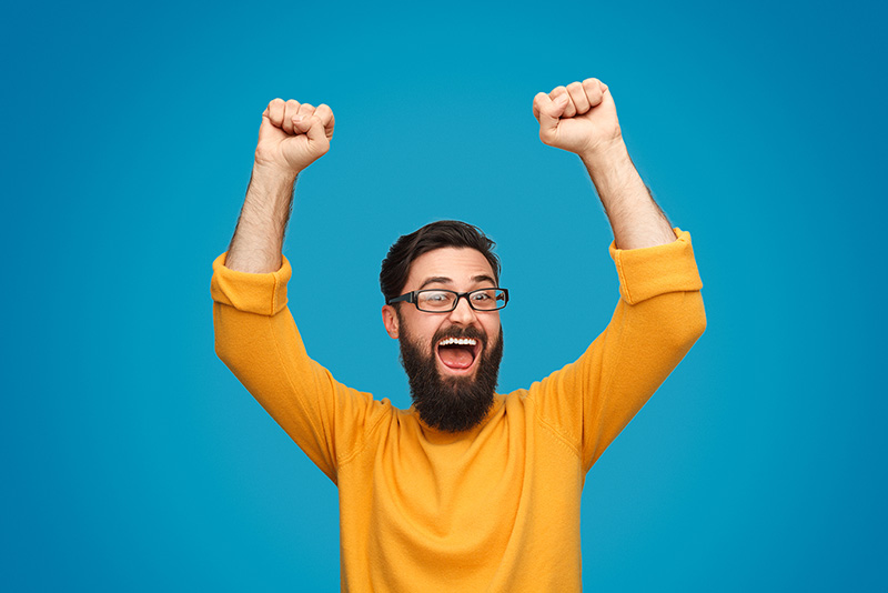 Man with arms in the air celebrating no guarantor car finance approval
