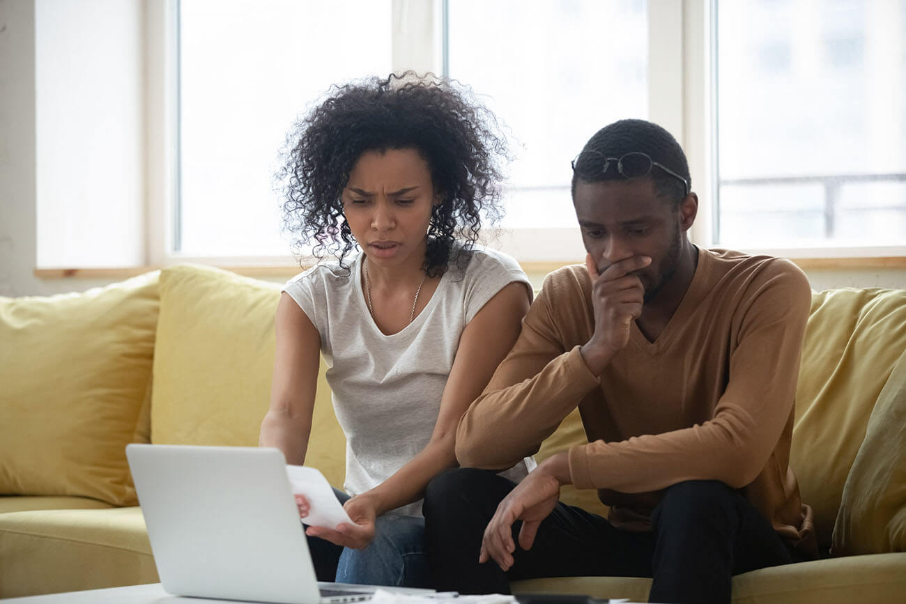 Couple sitting on sofa looking concerned they didn't choose cheaper Manchester car finance