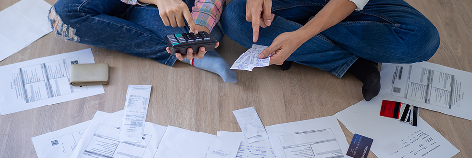 Couple sitting on floor with paperwork for no credit score car finance