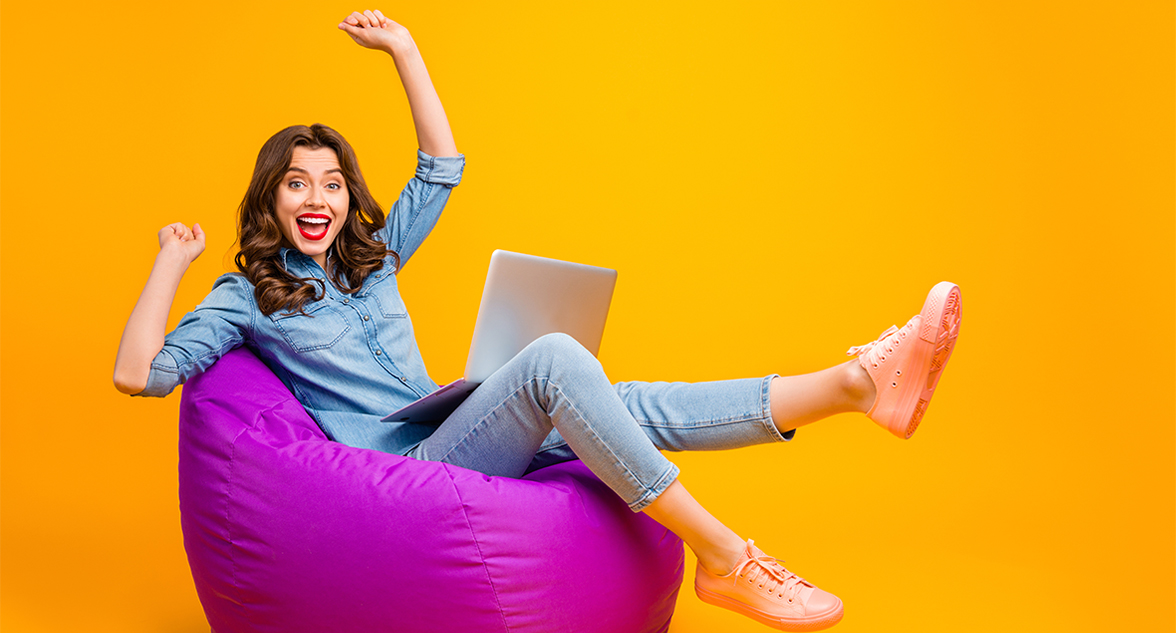 Woman sitting on bean bag with laptop happy with no guarantor car finance approval