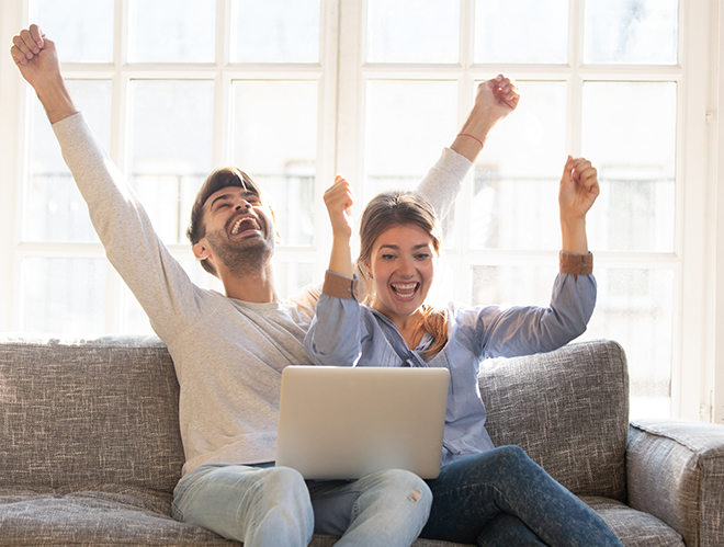 Happy couple with laptop celebrating on sofa no credit check car loans approval