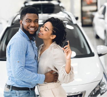 Happy couple standing in car showroom approved for a bad credit car loan