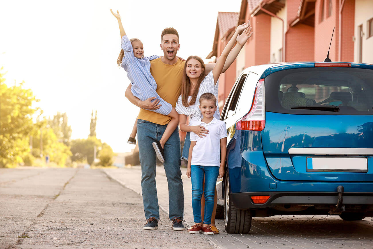Young family waving whilst standing next to car purchased with used car finance